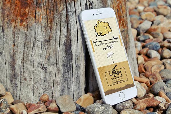 موکاپ گوشی موبایل آیفون در کنار تیرک چوبی بر روی سنگریزه