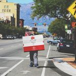 موکاپ تابلو و پوستر بزرگ در دست مرد در خیابان
